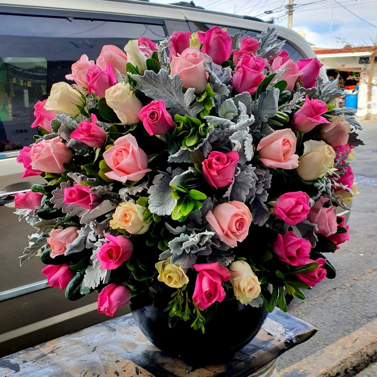 Arreglo floral de rosas rosas en esfera de cristal