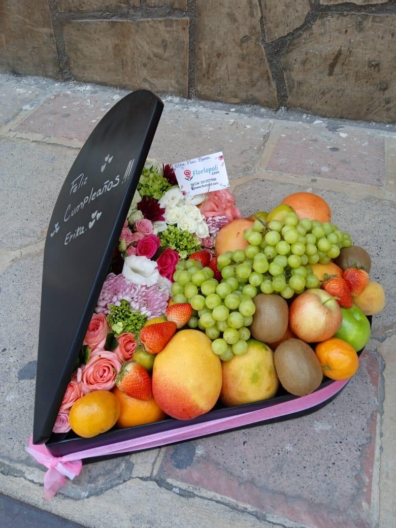 Canasta de frutas en forma de corazon y flores finas.